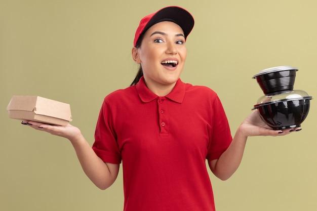 Gelukkige jonge leveringsvrouw in rood uniform en pet die voedselpakketten houden die voorzijde met glimlach op gezicht bekijken die zich over groene muur bevinden