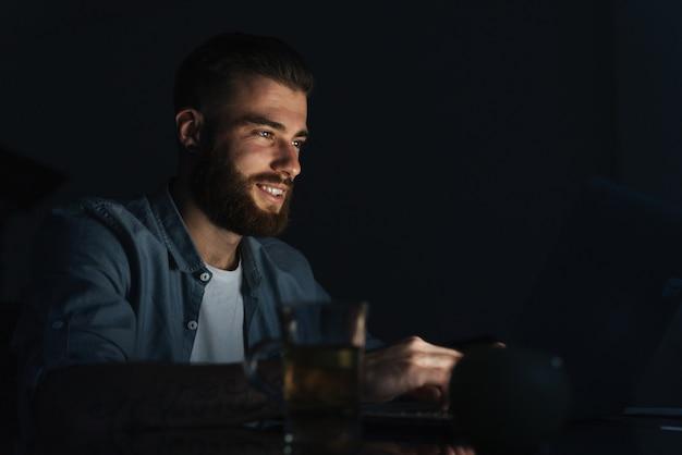 Gelukkige jonge man aan het werk op een laptop terwijl hij 's nachts binnenshuis aan tafel zit