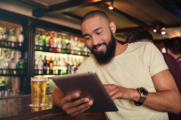 Gelukkige jonge man die bier drinkt in de pub en tablet gebruikt