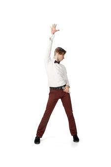 Gelukkige jonge man die danst in vrijetijdskleding of pak die legendarische bewegingen van beroemdheden opnieuw maakt