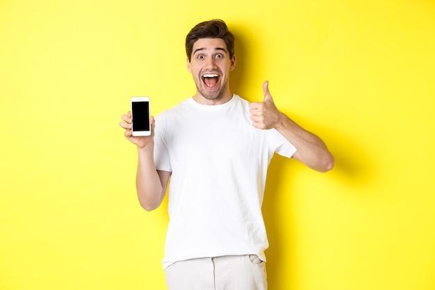 Gelukkige jonge man die duim omhoog en het scherm van de mobiele telefoon toont, applicatie of internetwebsite aanbeveelt, staande over gele achtergrond