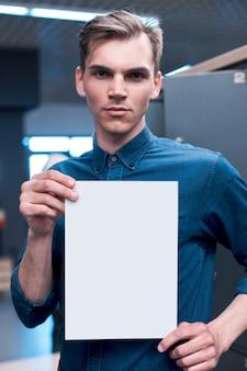 Gelukkige jonge man die een bordje toont en weergeeft dat klaar is voor uw tekst van het product