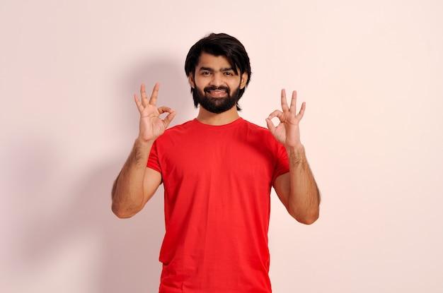Gelukkige jonge man die een goed teken toont met beide handen gebaren en glimlachen, alles komt goed