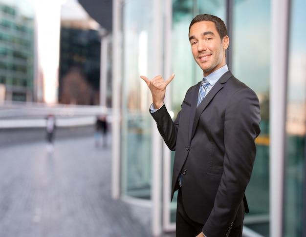 Gelukkige jonge man die een oproep gebaar doet