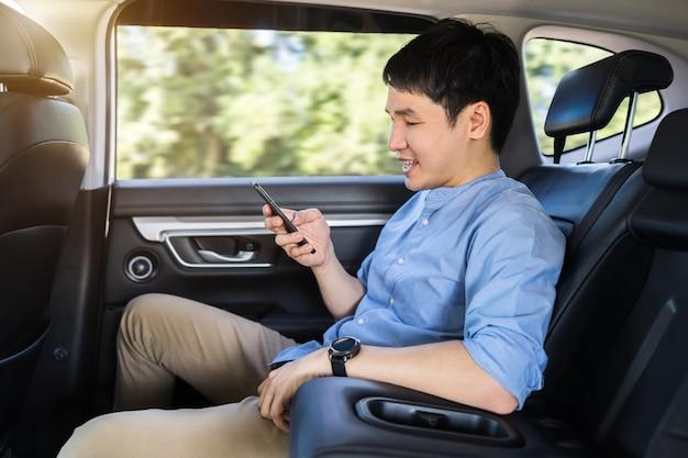 Gelukkige jonge man die een smartphone gebruikt terwijl hij op de achterbank van de auto zit