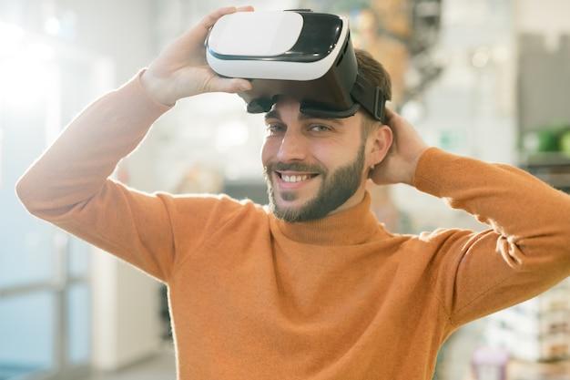 Gelukkige jonge man die je met een glimlach bekijkt terwijl hij de vr-headset opstijgt na het bekijken van virtueel assortiment