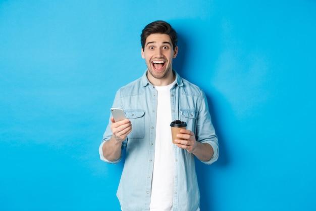 Gelukkige jonge man die koffie drinkt en mobiele telefoon gebruikt, er opgewonden uitziet, tegen een blauwe achtergrond staat