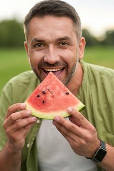 Gelukkige jonge man die naar de camera kijkt terwijl hij watermeloen eet in het groene park op een zomerdag