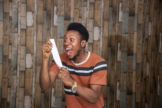 Gelukkige jonge man die naar een stuk papier kijkt
