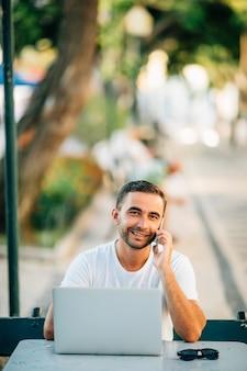 Gelukkige jonge man die op laptop werkt en op de mobiele telefoon praat terwijl hij buiten aan de houten tafel zit