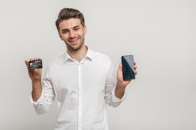 Gelukkige jonge man die plastic creditcard toont terwijl hij een mobiele telefoon met een zwart scherm vasthoudt