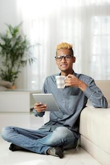Gelukkige jonge man die thuis op de vloer rust en een e-boek leest en een kopje thee of warme chocolademelk drinkt