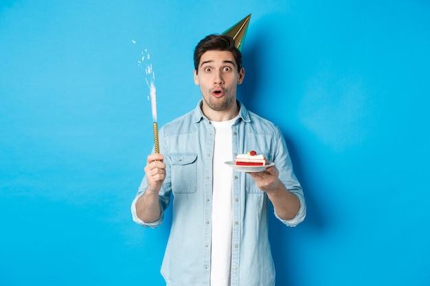 Gelukkige jonge man die verjaardag viert in feestmuts, verjaardagstaart vasthoudt en glimlacht, staande over blauwe achtergrond