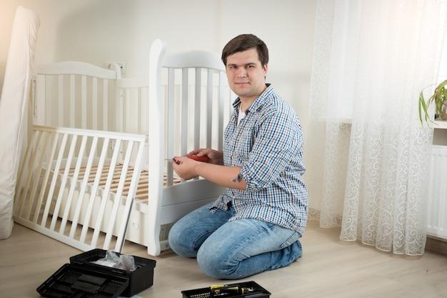 Gelukkige jonge man die witte houten wieg in de kinderkamer monteert