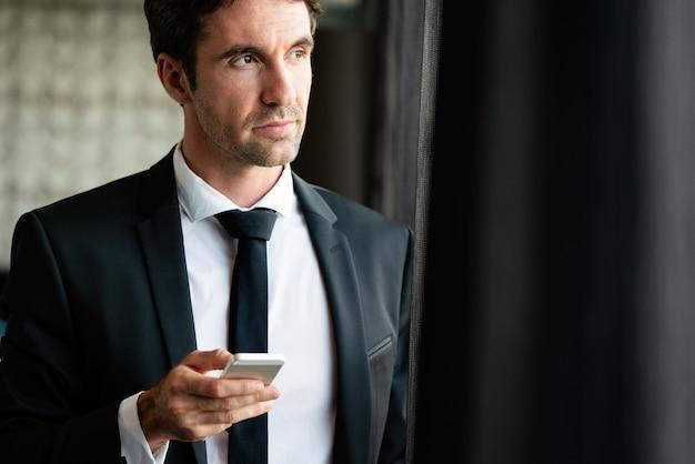 Gelukkige jonge man die zijn smartphone op kantoor gebruikt