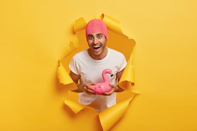 Gelukkige jonge man draagt rubberen roze badmuts, draagt een wit t-shirt, houdt zwemring vast in de vorm van een flamingo