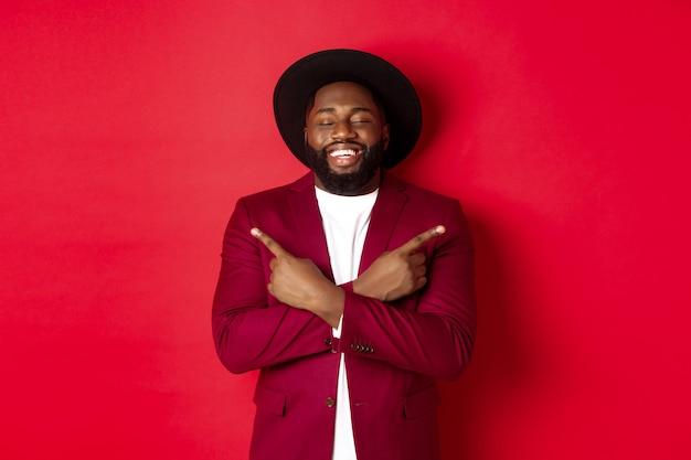 Gelukkige jonge man droomt en wijst met de vingers zijwaarts, sluit de ogen en glimlacht, toont twee dingen, staande over rode achtergrond.