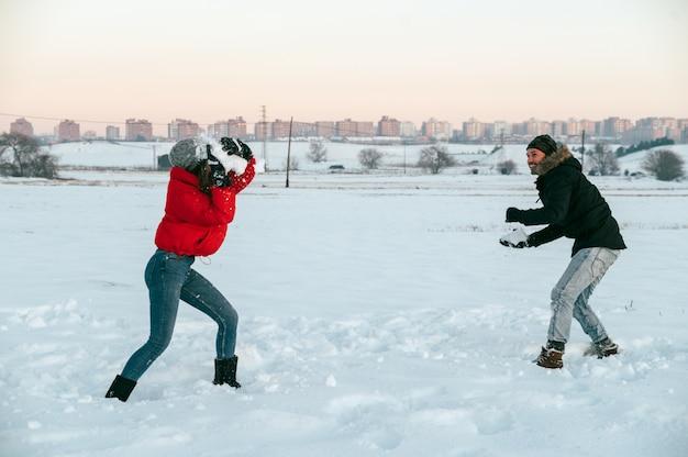 Gelukkige jonge man en vrouw in warme kleren sneeuwballen gooien met elkaar in veld in de buurt van de stad