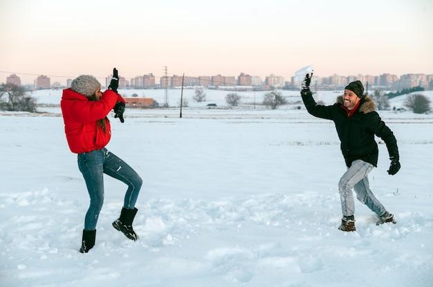 Gelukkige jonge man en vrouw in warme kleren sneeuwballen gooien met elkaar terwijl ze plezier hebben in het veld in de buurt van de stad