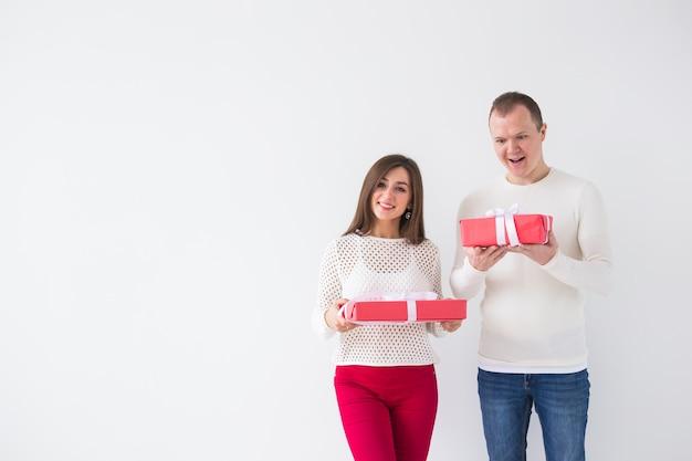 Gelukkige jonge man en vrouw met rode giftdozen