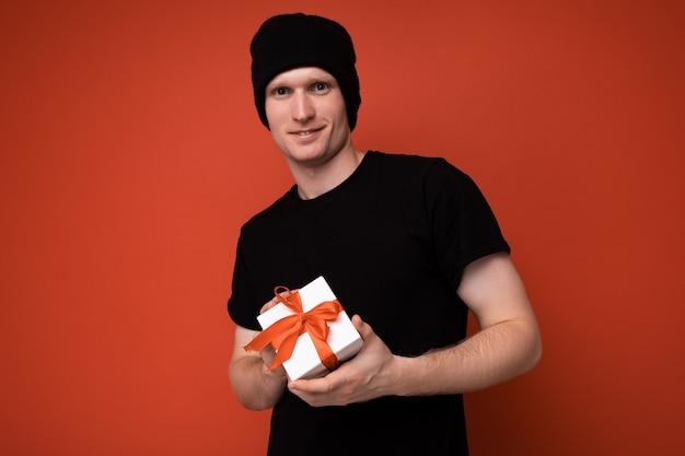 Gelukkige jonge man geïsoleerd op rode achtergrond muur met zwarte hoed en zwart