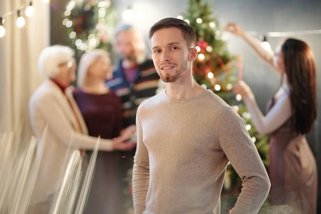 Gelukkige jonge man in beige pullover die zich met vrouwen bevindt die firtree vóór kerstmis verfraaien