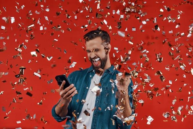 Gelukkige jonge man in casual kleding met smartphone en gebaren terwijl hij staat