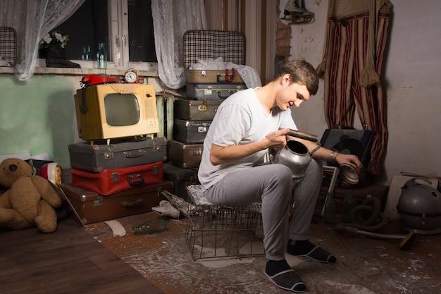 Gelukkige jonge man in casual outfit zittend op kooi, met ongebruikte waterkoker in de rommelkamer
