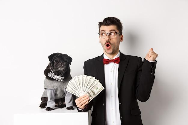 Gelukkige jonge man in pak verdient geld met zijn hond. guy verheugt zich, houdt dollars vast en staart naar links, zwarte mopshond in kostuum starend naar camera, witte achtergrond