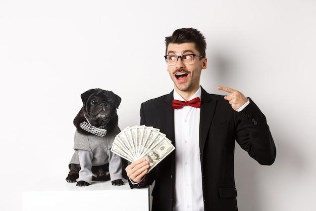 Gelukkige jonge man in pak verdient geld met zijn hond. guy verheugt zich, houdt dollars vast en wijst naar links, zwarte mopshond in kostuum starend naar camera, witte achtergrond.
