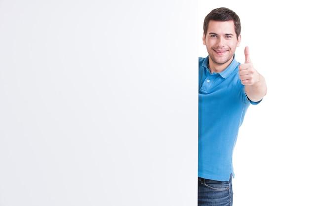 Gelukkige jonge man kijkt uit van lege banner met duim omhoog - geïsoleerd op wit.