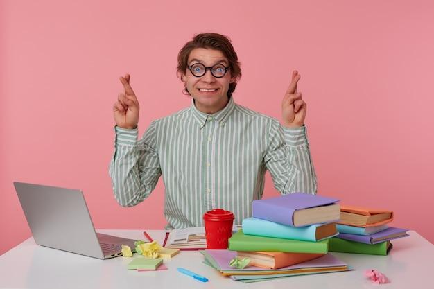 Gelukkige jonge man met donker haar zittend aan de werktafel, vingers kruisen voor geluk en vrolijk lacht