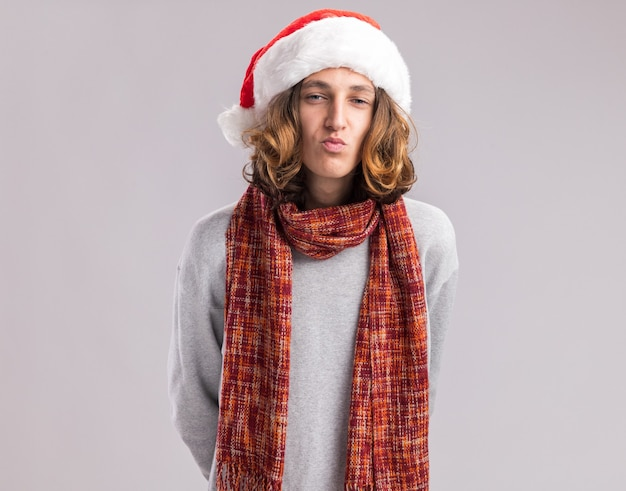 Gelukkige jonge man met een kerstmuts met een warme sjaal om zijn nek en houdt zijn lippen alsof hij over een witte muur gaat kussen kiss