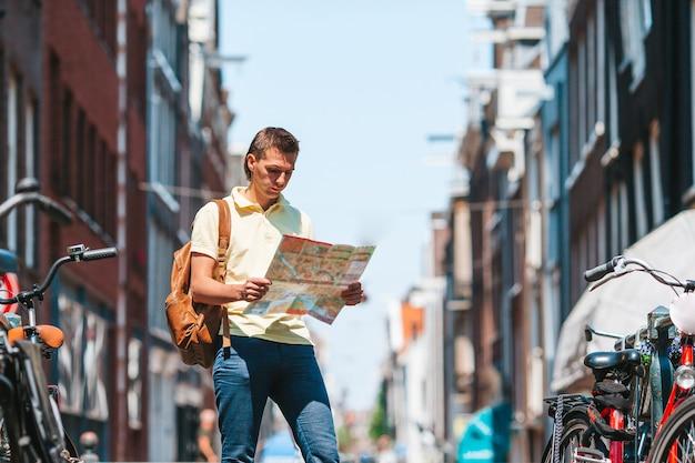 Gelukkige jonge man met een stadsplattegrond in de europese stad