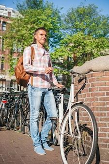 Gelukkige jonge man met een stadsplattegrond op de fiets in de europese stad