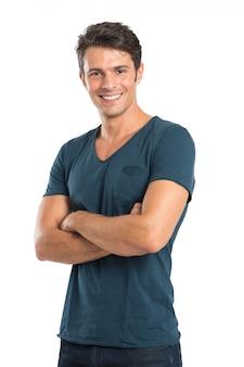 Gelukkige jonge man met gekruiste arm geã ¯ soleerd op witte achtergrond
