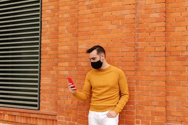 Gelukkige jonge man met gezichtsmasker met smartphone in de stad. moderne stijlvolle gele kleding. medisch masker en levensstijl.