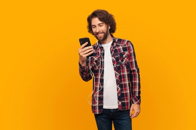 Gelukkige jonge man met krullend haar in shirt luistert naar muziek in koptelefoon en houdt smartphone vast