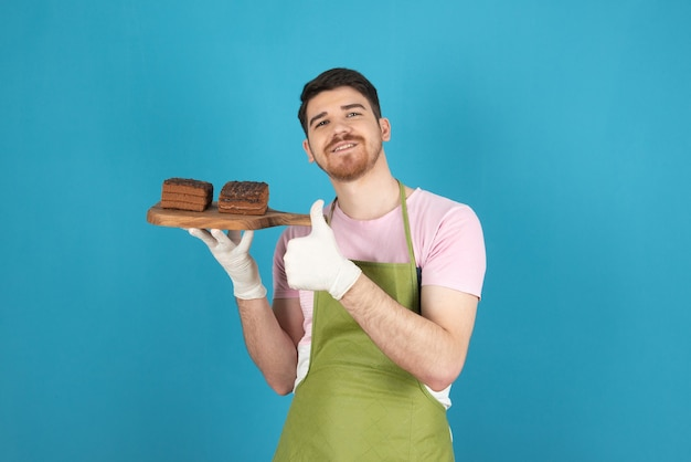 Gelukkige jonge man met plakjes chocoladetaart op een blauw.
