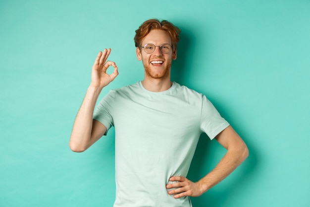Gelukkige jonge man met rood haar en baard, bril en t-shirt dragen, tevreden glimlachen en ok teken tonen, ja zeggen, goedkeuren en akkoord gaan, staande over turkooizen achtergrond