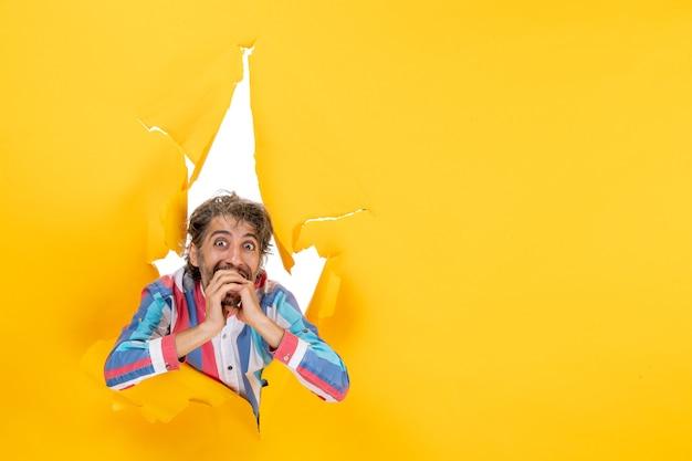 Gelukkige jonge man poseert in een gescheurde gele papieren gatachtergrond