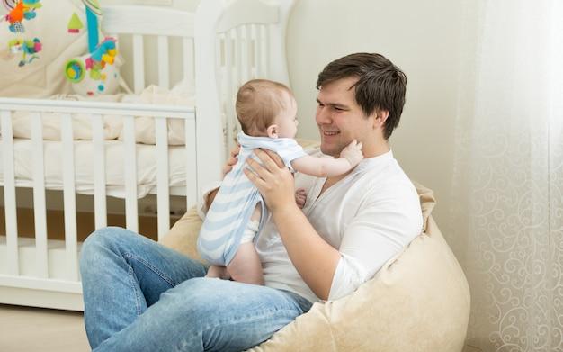 Gelukkige jonge man speelt met zijn baby in de slaapkamer