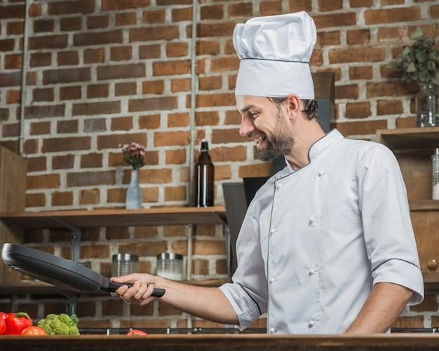 Gelukkige jonge mannelijke chef-kok die voedsel in de keuken voorbereiden