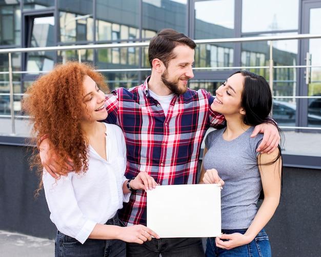 Gelukkige jonge mannelijke en vrouwelijke vrienden die leeg wit aanplakbiljet tonen