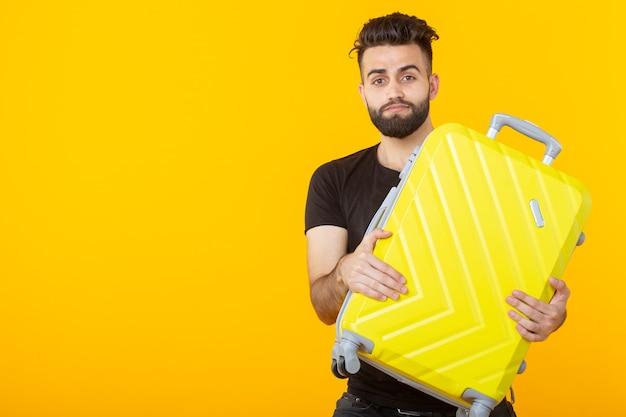 Gelukkige jonge mannelijke hipster met een baard die een gele koffer op een geel oppervlak houdt en zich verheugt