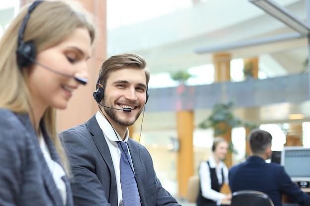 Gelukkige jonge mannelijke klantenservicemedewerker die op kantoor werkt.