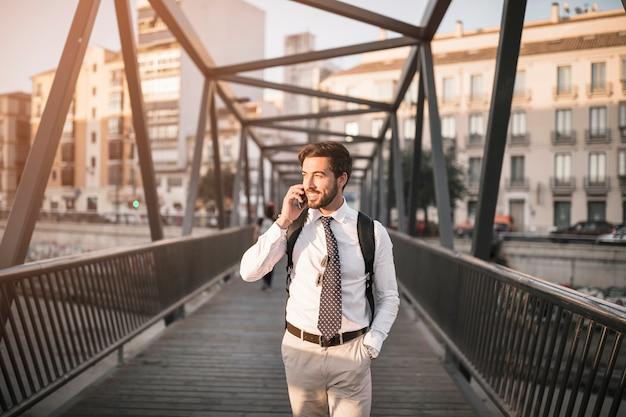 Gelukkige jonge mannelijke reis die zich op brug bevindt die op cellphone spreekt