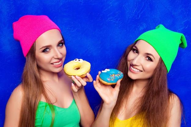 Gelukkige jonge meisjes die in hoeden zoete donutes houden