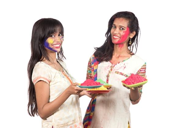 Gelukkige jonge meisjes die pret met kleurrijk poeder hebben bij holi-festival van kleuren