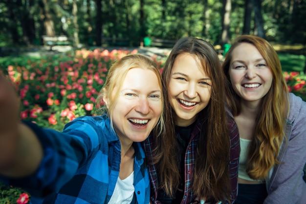 Gelukkige jonge meisjes hebben plezier lachen en het nemen van selfies op een smartphone in het park